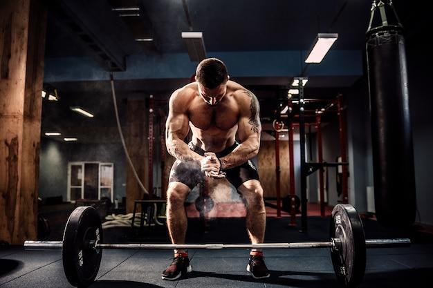 Gespierde fitness man voorbereiding op deadlift een barbell boven zijn hoofd in moderne fitnesscentrum. functionele training.