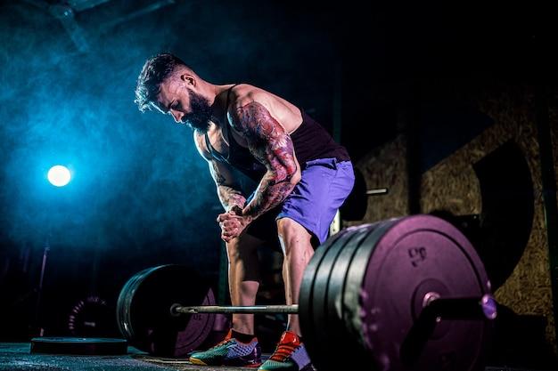 Gespierde fitness man voorbereiding op deadlift van een barbell in moderne fitnesscentrum. functionele training.