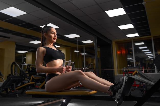 Gespierde fitness vrouw atleet zwaar gewicht oefening voor rug op machine met kabel in de sportschool