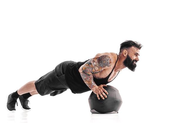 Gespierde getatoeëerde bebaarde man fitness gewichten uit te oefenen medicine ball push-ups oefeningen Premium Foto
