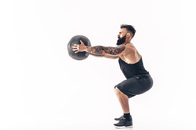 Gespierde getatoeëerde bebaarde man uit te oefenen fitness gewichten medicine ball geïsoleerd op een witte muur.