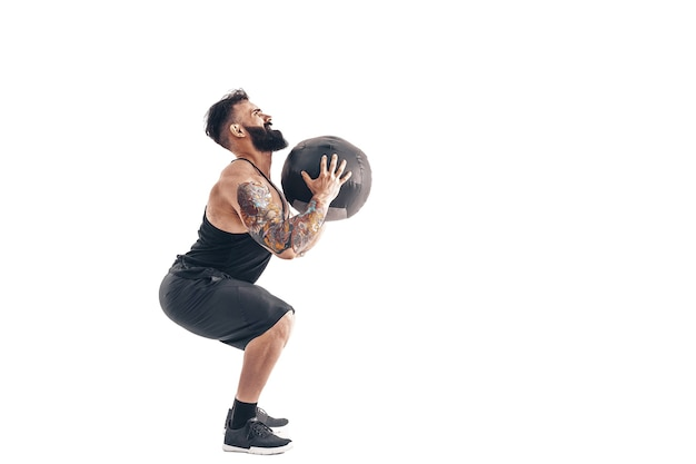 Gespierde getatoeëerde bebaarde man uit te oefenen fitness gewichten medicine ball in studio geïsoleerd op een witte muur.