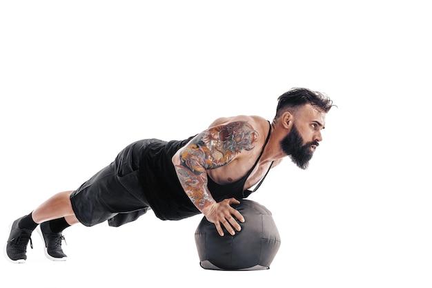 Gespierde getatoeëerde bebaarde man uit te oefenen fitness gewichten medicine ball push-ups oefeningen in geïsoleerd op een witte muur.
