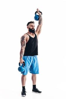 Gespierde getatoeëerde bebaarde mannelijke atleet bodybuilder training met kettlebell