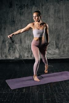 Gespierde jonge atletische vrouw met een perfect mooi lichaam die sportkleding draagt die traint met een rubberen weerstandsband. kaukasische vrouwelijke fitnesstraining met stretching expander in studio.