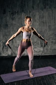 Gespierde jonge atletische vrouw met een perfect mooi lichaam die sportkleding draagt die traint met een weerstandsband die op de mat staat. kaukasische vrouwelijke fitnesstraining met stretching expander in studio.