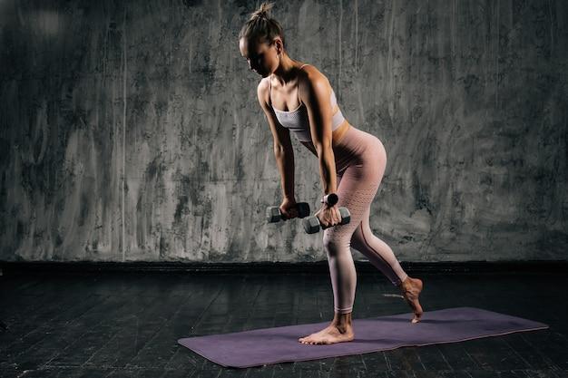 Gespierde jonge atletische vrouw met perfect lichaam in sportkleding die traint met halters.