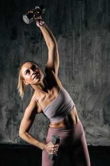 Gespierde jonge atletische vrouw met perfect mooi lichaam in sportkleding die de kettlebell overhead opheft tijdens krachttraining. kaukasische fitness vrouw poseren in studio met donkere achtergrond.
