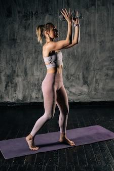 Gespierde jonge atletische vrouw met perfect mooi lichaam in sportkleding die kettlebell boven het hoofd opheft