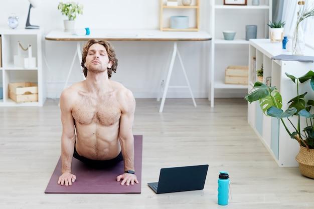 Gespierde jonge man doet yoga op oefeningsmat online in de kamer