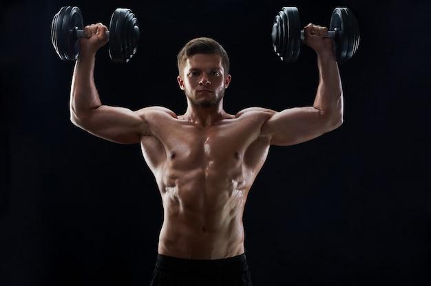 Gespierde jonge man tillen gewichten op zwarte achtergrond