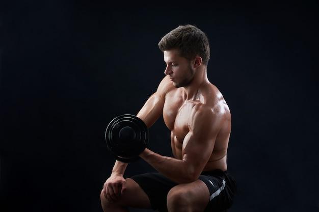 Gespierde jonge man tillen gewichten op zwarte muur