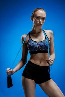 Gespierde jonge vrouw atleet met een springtouw op blauw