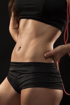 Gespierde jonge vrouw atleet met een springtouw op zwart