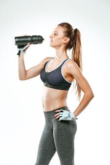 Gespierde jonge vrouw atleet met een water op black