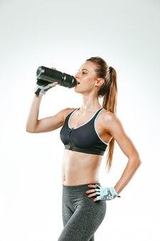 Gespierde jonge vrouw atleet met een water op zwart