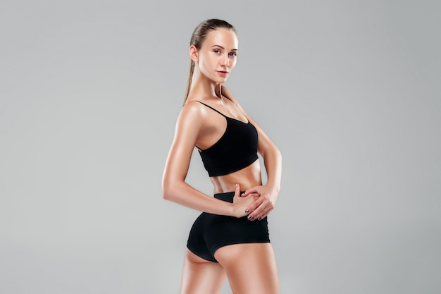 Gespierde jonge vrouw atleet op grijs