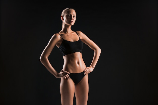 Gespierde jonge vrouw atleet op zwart