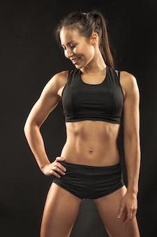Gespierde jonge vrouw atleet op zwarte muur