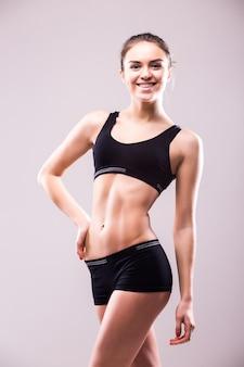 Gespierde jonge vrouw atleet permanent neerkijkt met haar handen op de heupen op grijze muur