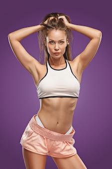 Gespierde jonge vrouw atleet poseren in studio op lila achtergrond