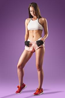 Gespierde jonge vrouw atleet poseren op lila ruimte