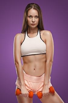 Gespierde jonge vrouw atleet poseren