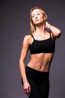 Gespierde jonge vrouw atleet staande op grijze muur