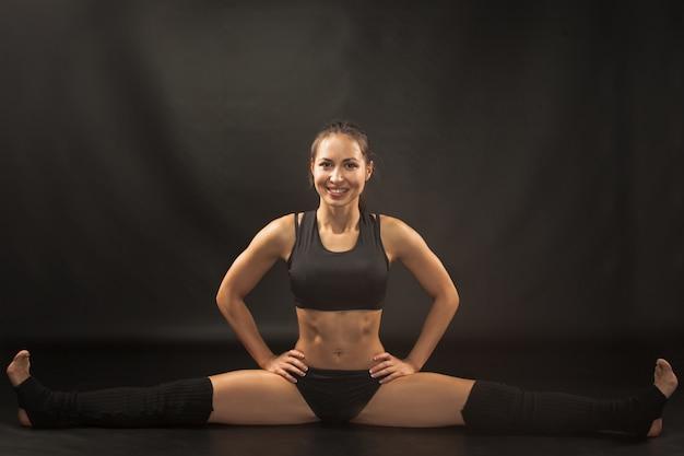 Gespierde jonge vrouw atleet zit in de splitsing op zwart