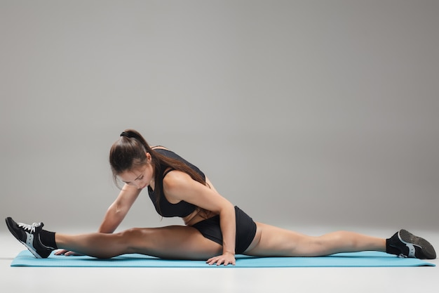 Gespierde jonge vrouw atleet zitten in de spleet op grijs