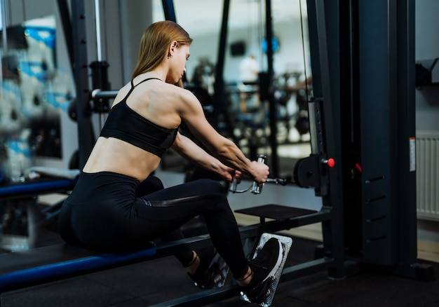 Gespierde jonge vrouw in zwarte sportkleding en trainers doet intensieve training door gewichten te trekken in de sportschool.