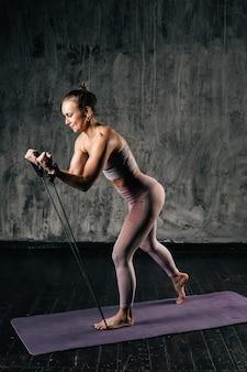 Gespierde jonge vrouw met mooi lichaam in sportkleding die traint met een rubberen weerstandsband