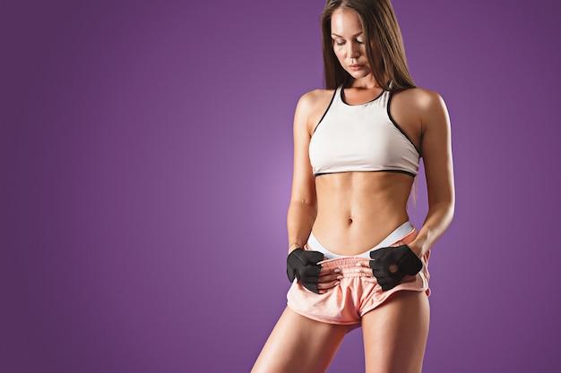 Gespierde jonge vrouwelijke atleet poseren