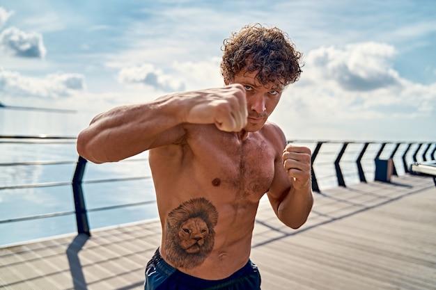 Gespierde jongeman atleet staat en oefent schaduwboksen buiten vroeg in de ochtend op de pier