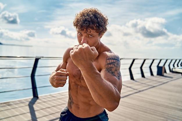 Gespierde jongeman atleet staat en oefent schaduwboksen buiten vroeg in de ochtend op pi...
