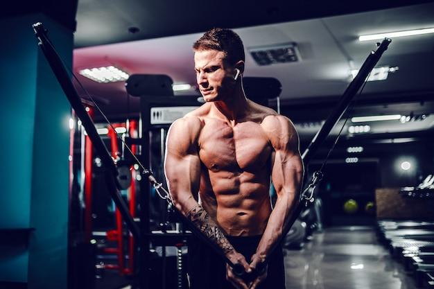Gespierde lichaamsbouwer die bij de gymnastiek uitwerkt die borstvliegoefeningen op de machine van de draadkabel doet