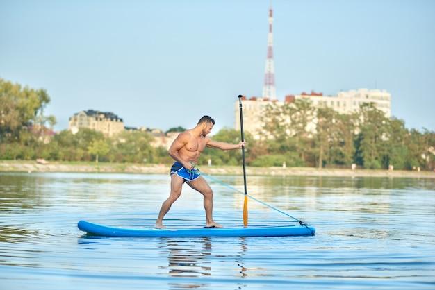 Gespierde man bezig met sportoefeningen aan boord in het midden van het stadsmeer.