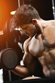 Gespierde man bodybuilder doen oefeningen met halters close-up in de sportschool. atletisch lichaam, gezonde levensstijl, fitnessmotivatie, positief lichaam.