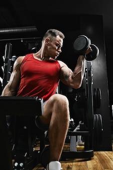 Gespierde man bodybuilder doen oefeningen met halters in de sportschool. atletisch lichaam, gezonde levensstijl, fitnessmotivatie, positief lichaam.