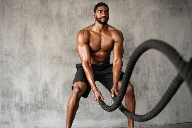 Gespierde man die aan het trainen is op de strijdtouwen in een sportschool