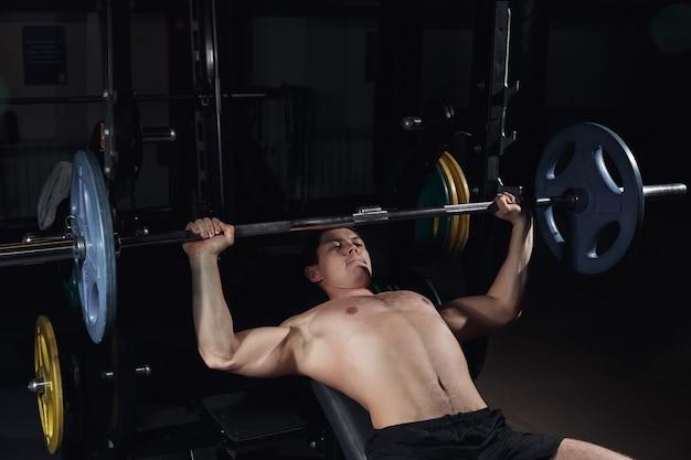 Gespierde man die zware oefening doet. atletische man oppompen van spieren op bankdrukken.