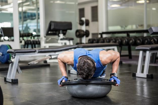 Gespierde man doen push-up met bosu bal in de sportschool