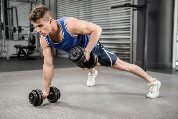 Gespierde man doen push-up met halters in de sportschool crossfit