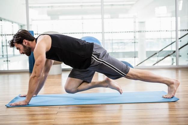 Gespierde man doen push-up op mat in de studio