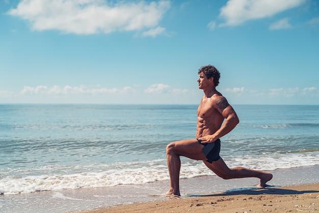Gespierde man doet oefening op strand lichaamstraining