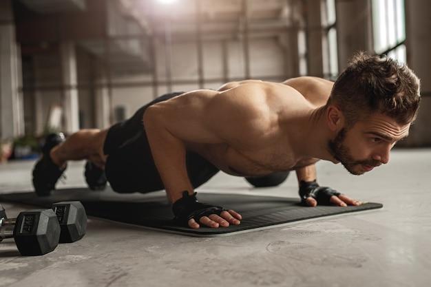 Gespierde man doet push-up oefening op mat in de buurt van halters tijdens intensieve fitnesstraining in grungy sportschool