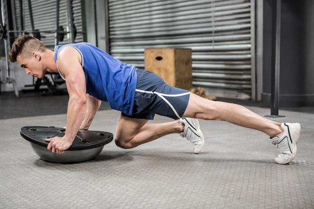 Gespierde man doet push up op bosu bal op de crossfit gym