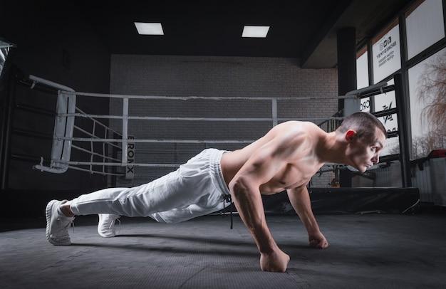 Gespierde man doet push-ups in de sportschool. geschiktheidsconcept. gemengde media