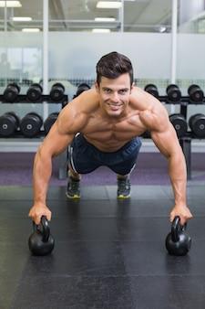 Gespierde man doet push ups met waterkoker klokken in de sportschool