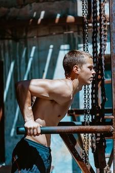 Gespierde man doet wat push-ups tegen de ijzeren kettingen